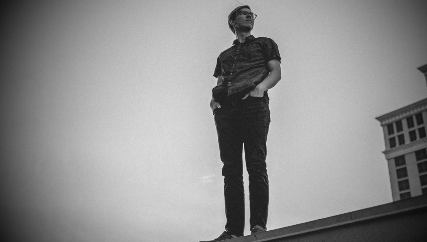 Man on a rooftop, looking back. A slightly adapted photo from Analise Benevides on Unsplash.