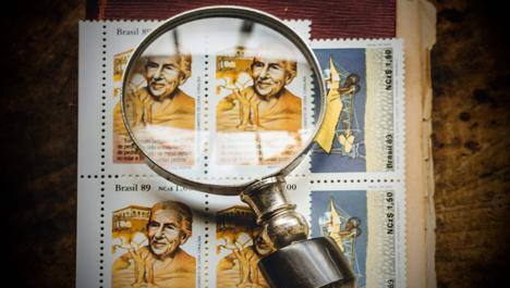 Magnifying glass with old vintage book and brazilian stamps. Photo by Koala on Unsplash.