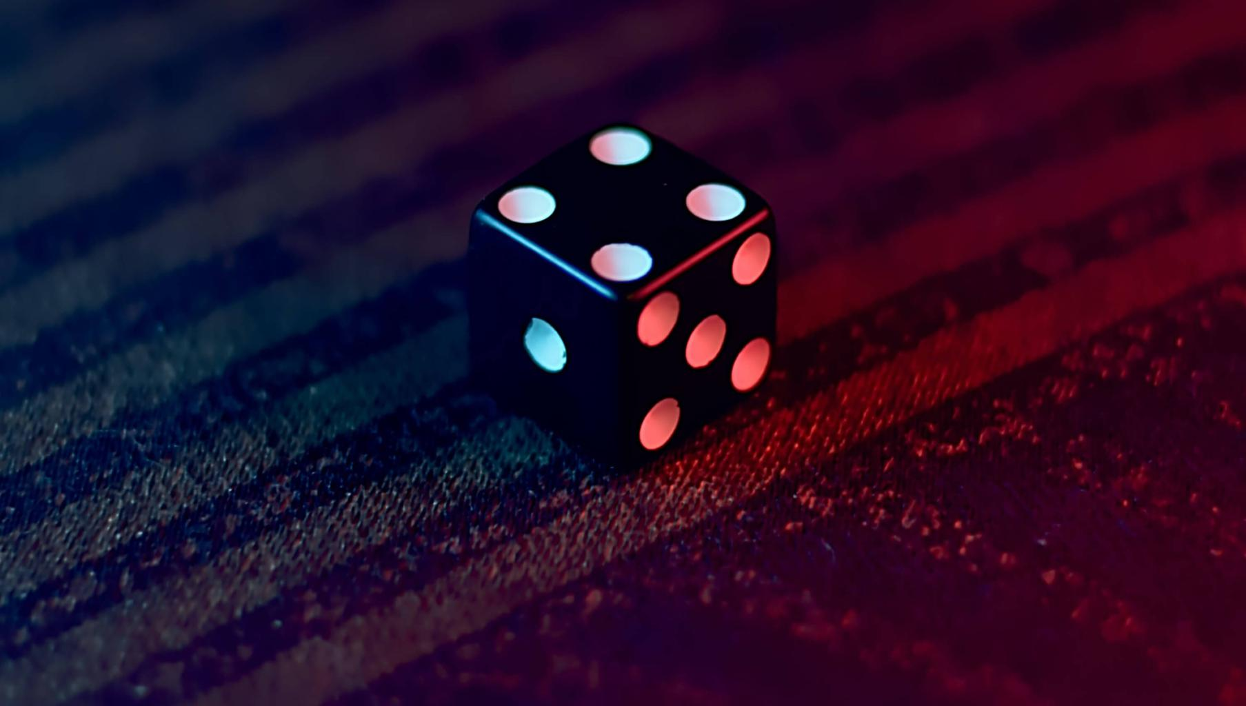 Dice on red textile. Photo by Joel Abraham on Unsplash.