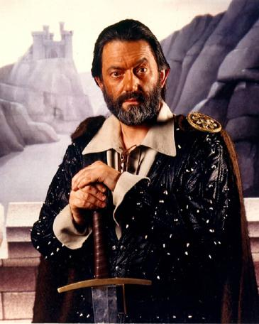 Full promotional shot of Treguard (Hugo Myatt), set against castle background.
