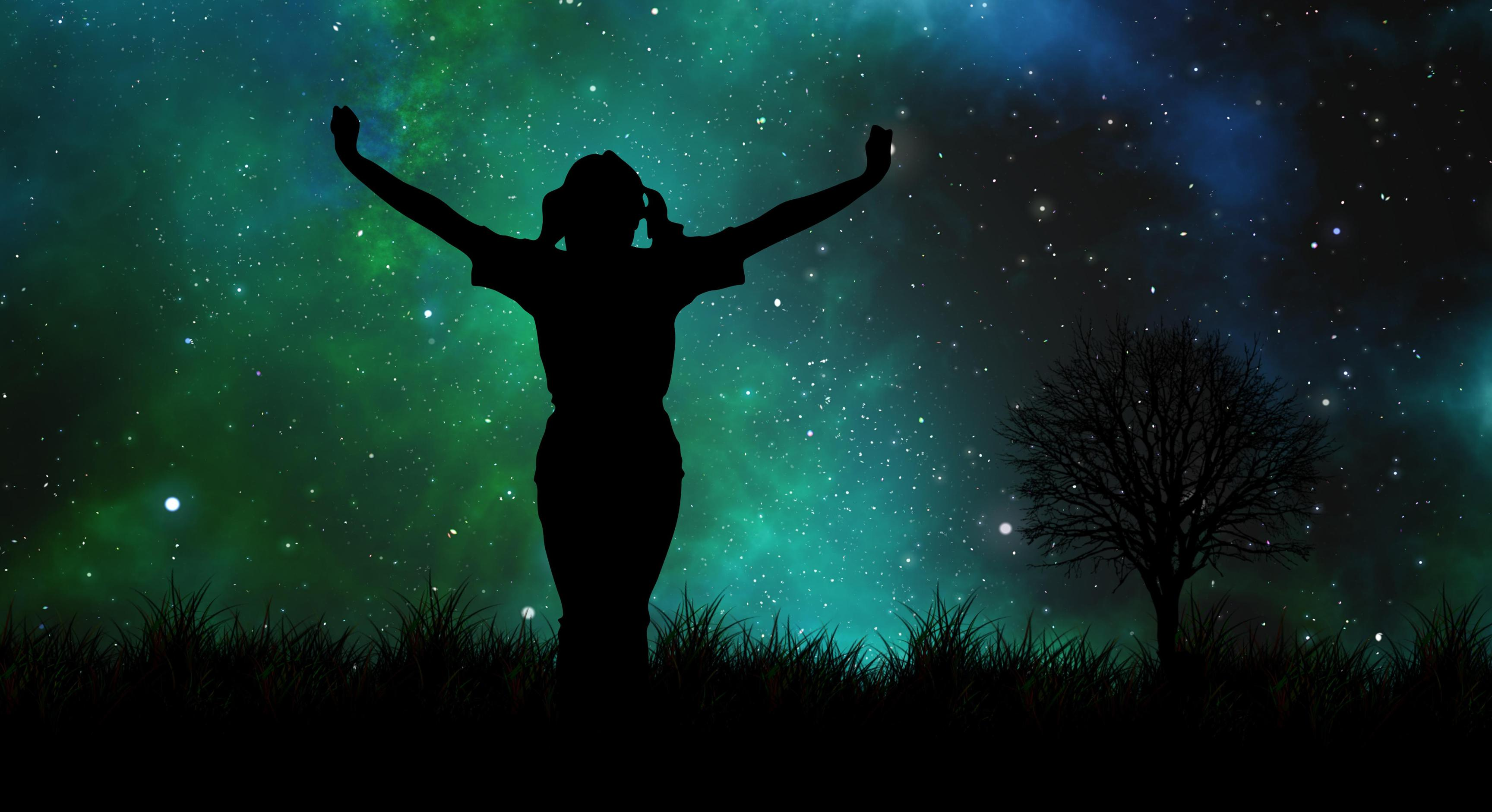 Silhouette of woman standing on hill in front of galaxy backdrop