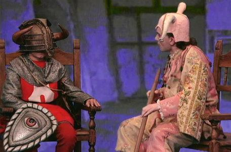 A jester sits with a knight in the second series of El Rescate del Talisman.